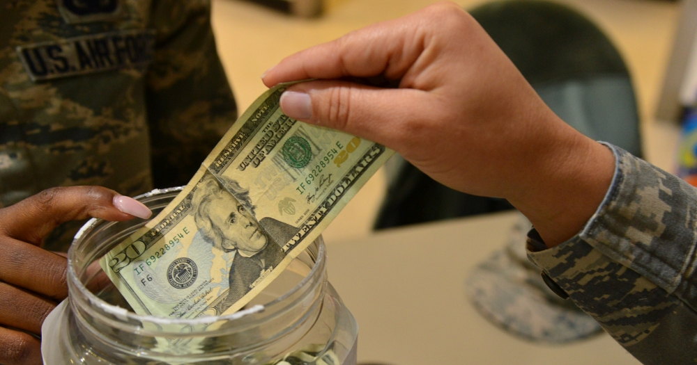 ofiara na tacę - jedna ręka wkłada banknot do słoika, zdjęcie: defense.gov, CC-0