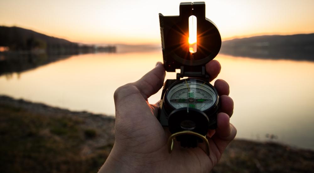 ręka trzymająca kompas nakierowana na słońce, zdjęcie tim-graf-unsplash CC-0